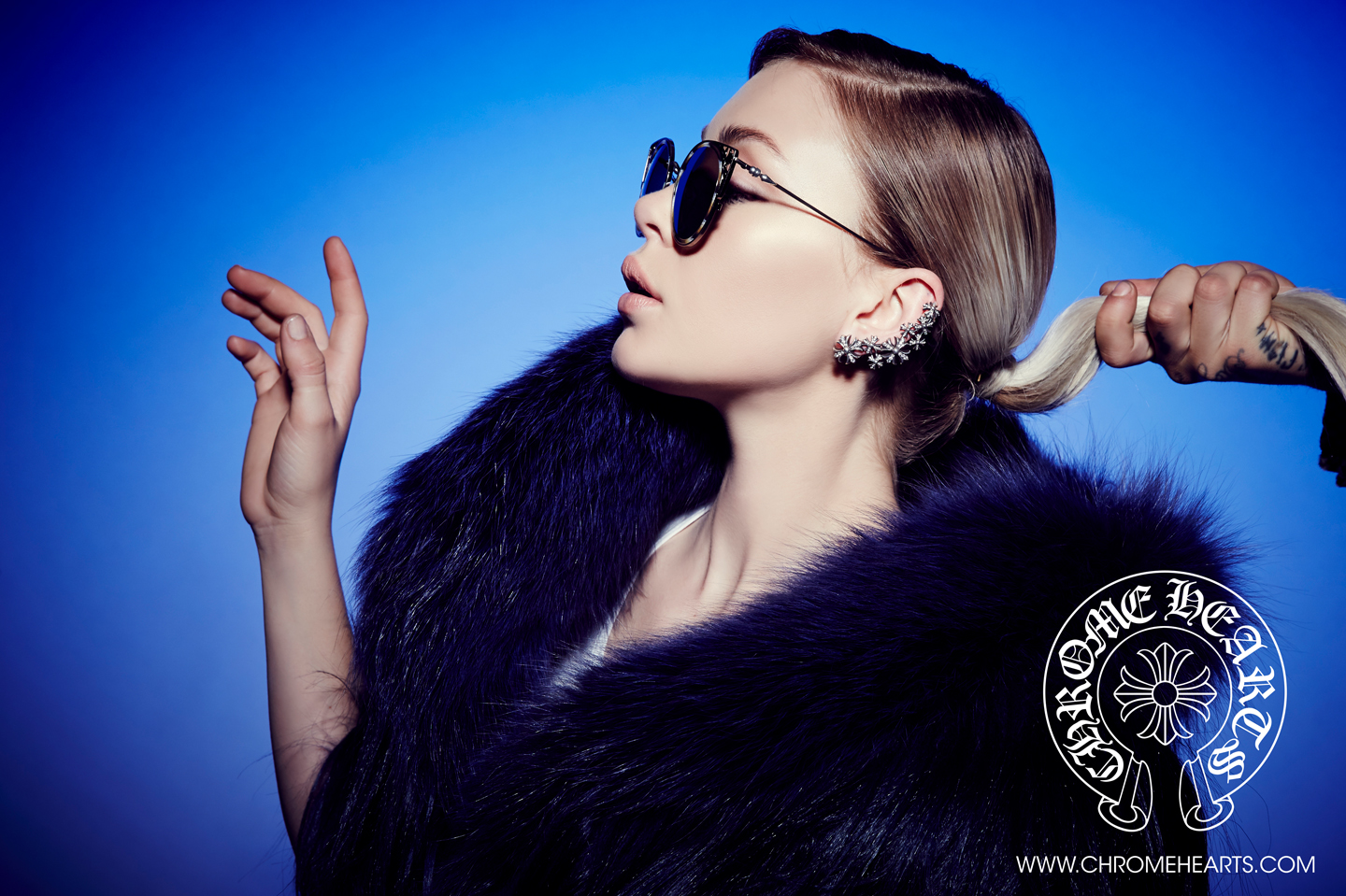 Lanna Lyon in CH glasses on blue backdrop | CHROME HEARTS Photography by Laurie Lynn Stark