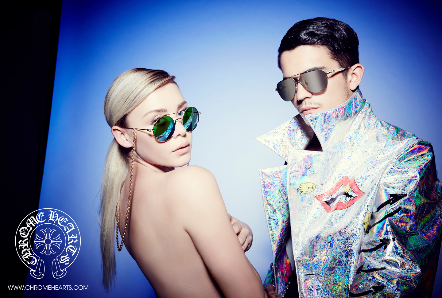Lanna Lyon x Payden Hayes in CH glasses on blue backdrop | Matt DiGiacomo Chomper Jacket | CHROME HEARTS Photography by Laurie Lynn Stark